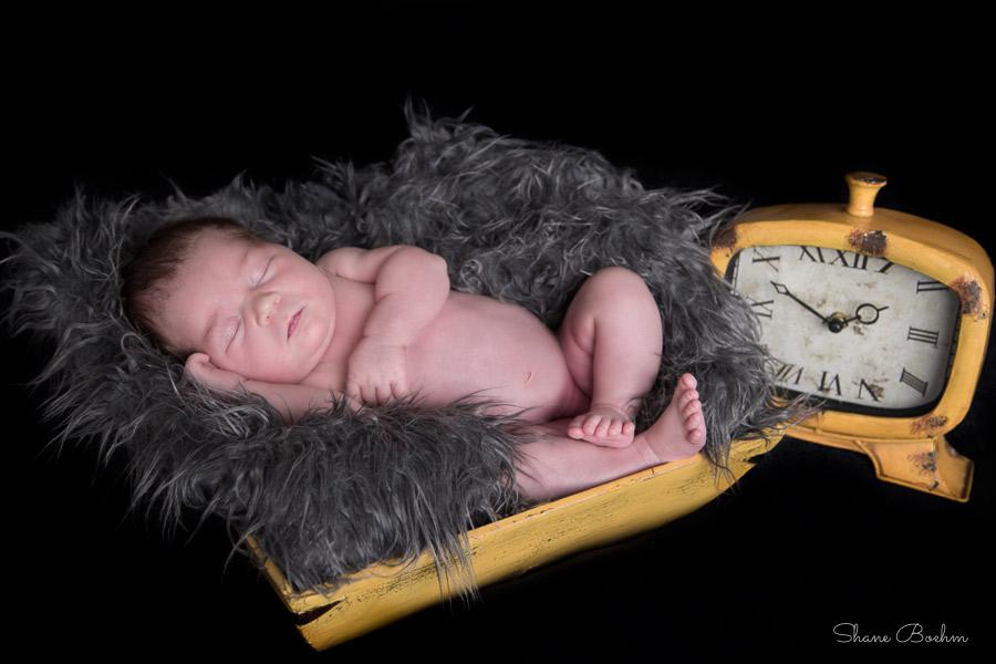 Newborn sleeping in yellow bowl next to clock
