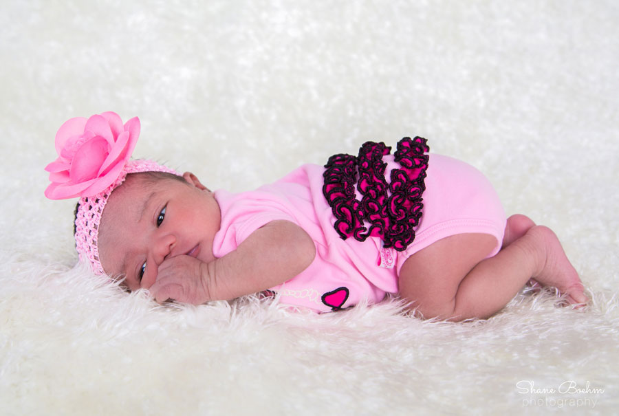 Newborn Lying Awake on Her Belly in Pink with Flower Headband